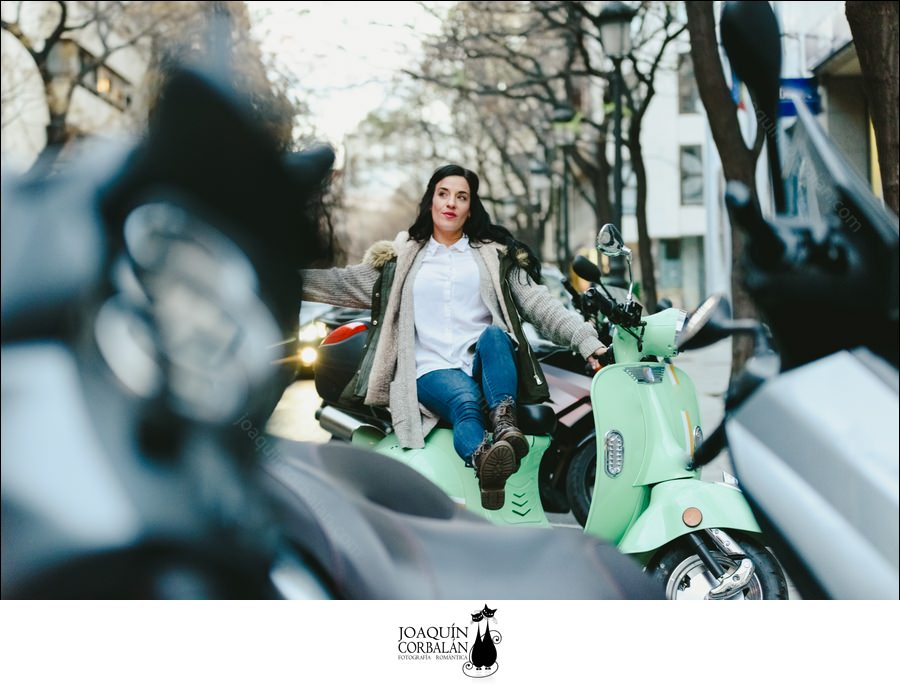 Brunette Woman Riding On A Scooter Parked On The Street Posing.