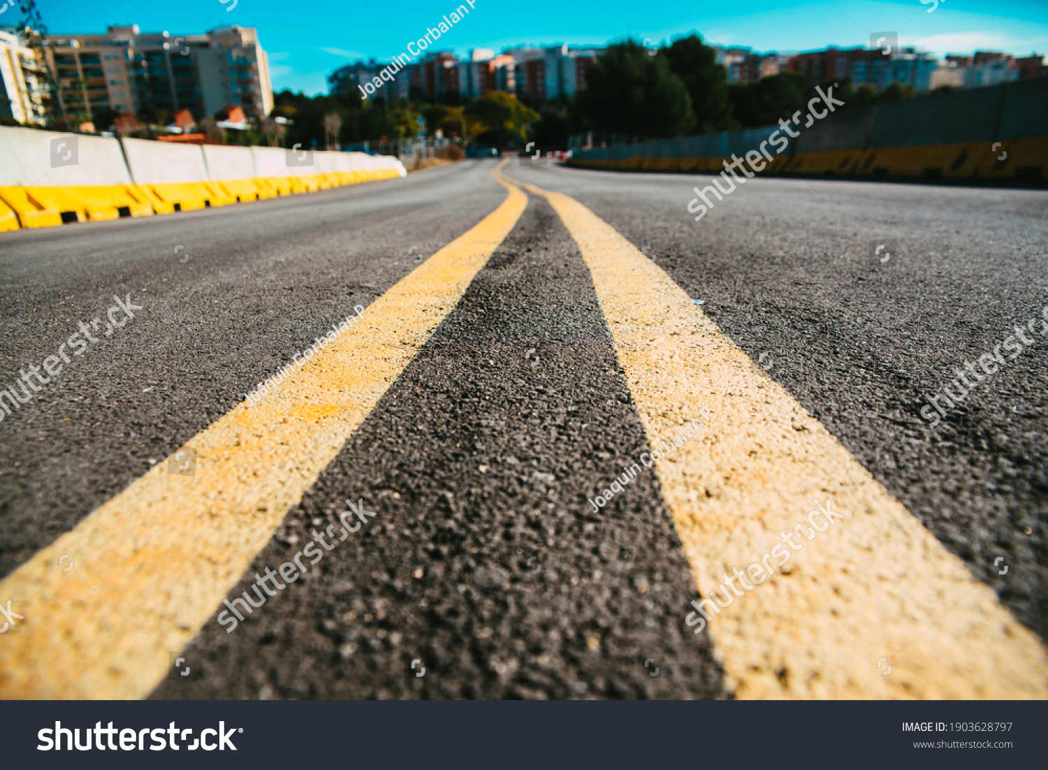 Stock Photo Double Yellow Line On The Black Asphalt Leading To The Entrance To The City 1903628797