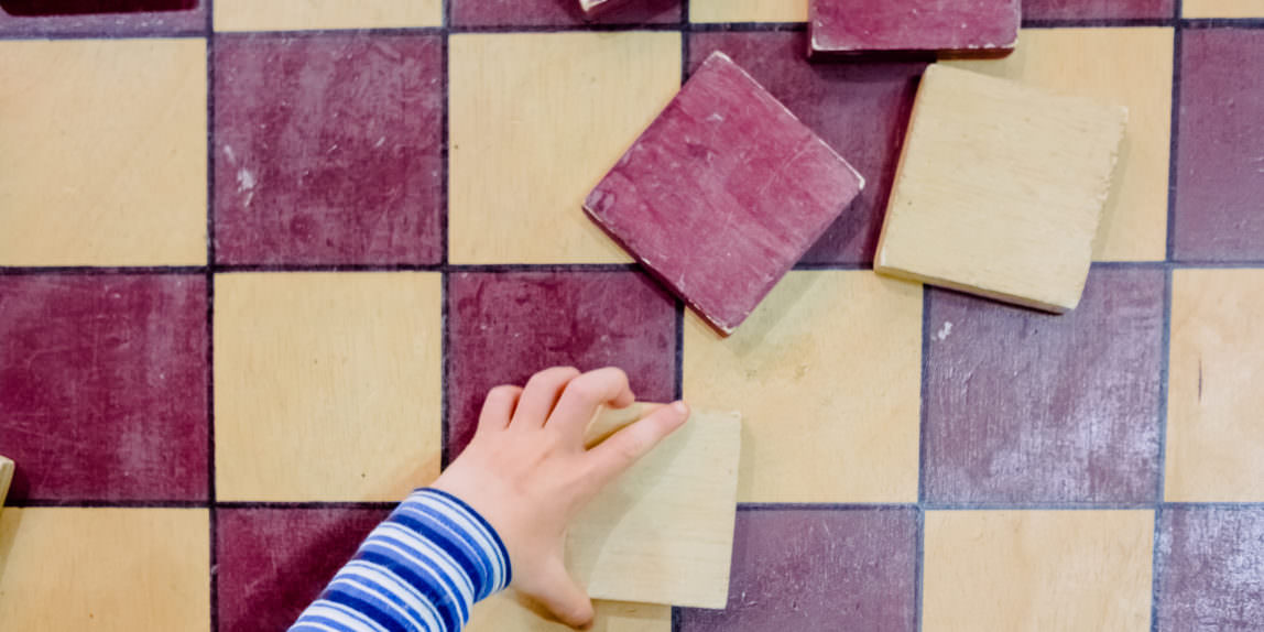 Child's Hand Places The Pieces Of A Checkers Game, Seen From Abo