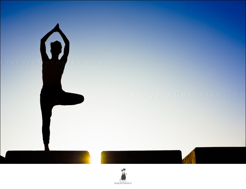 Silhouette Of A Man Practicing Yoga, Isolated Against The Blue Sky.
