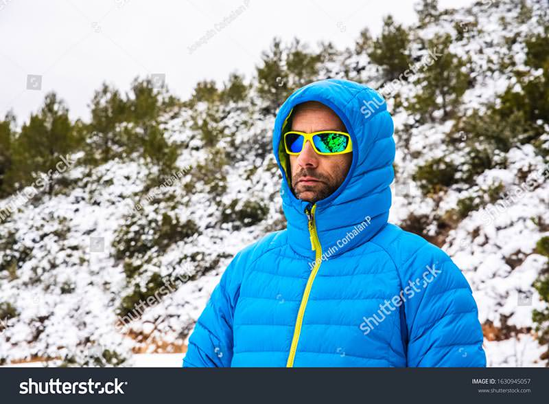 Stock Photo Hiker Walks Down The Mountain During A Snow Covered In A Down Coat 1630945057